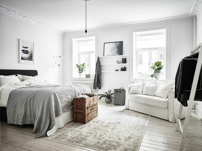 Zimmerdecke mit dekorativen Simsen, grau-weißes Teppich auf dem Holzboden, Holzständer für Kleider, Bild mit Frauengesicht mit schwarzem Lippenstift