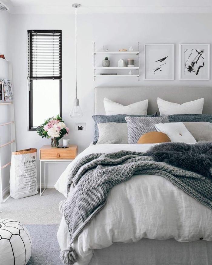 weißer Puff mit schwarzen Nähten, Fotowand aus Holz, graue Strickdecke mit Troddeln, graue Strickbezüge für dekorative Kissen, Blumenstrauß mit weißen und rosa Blumen