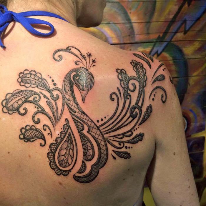tattoo freiheit, frau mit großer abstrakter tätowierung, pfau-motiv