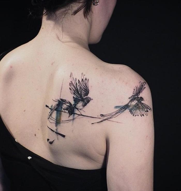 tattoo freiheit, frau mit schwarz-grauer tätowierung mit vogel-motiv am rücken