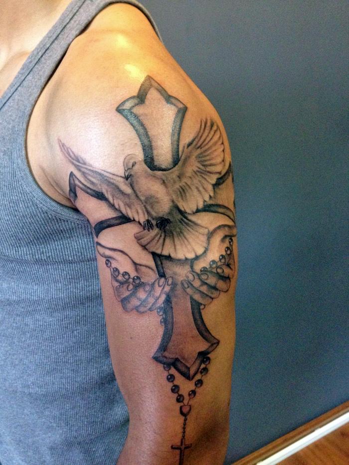 tattoo taube, mann mit großer 3d-tätowierung am arm, taube mit kreuz und hände