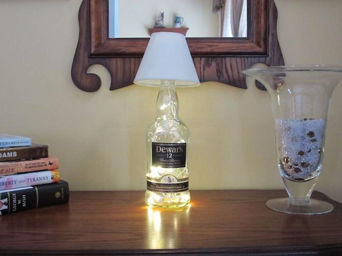 spiegel und ein tisch und eine diy lampe aus einer durchsichtigen glasflasche - lampen aus flaschen selber machen