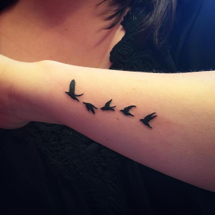 unterarm tattoo, kleine tattoo motive, schwarze fliegende vögel