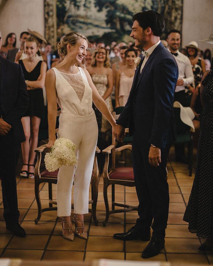 jumpsuit damen elegant knöchellanger einteiler in weiß für die braut fröhliches paar mann mit blauem anzug viele gäste hochzeit feiern