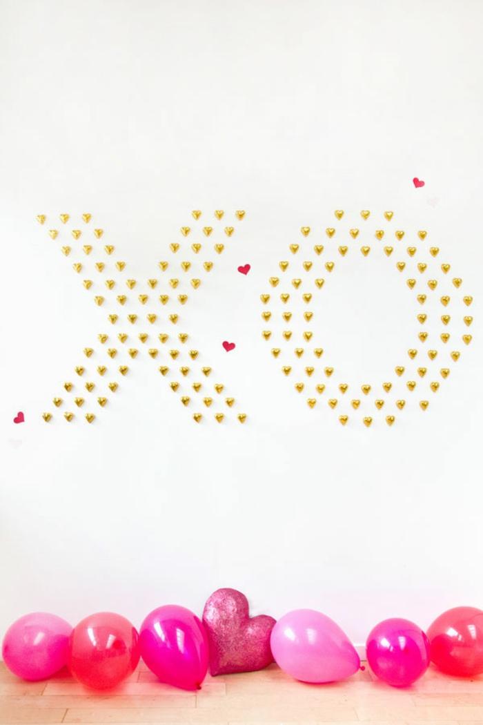 Aufschrift aus Schokoladen Herzen an der Wand, rote und rosafarbene Luftballons auf dem Boden, romantische Überraschung zum Valentinstag