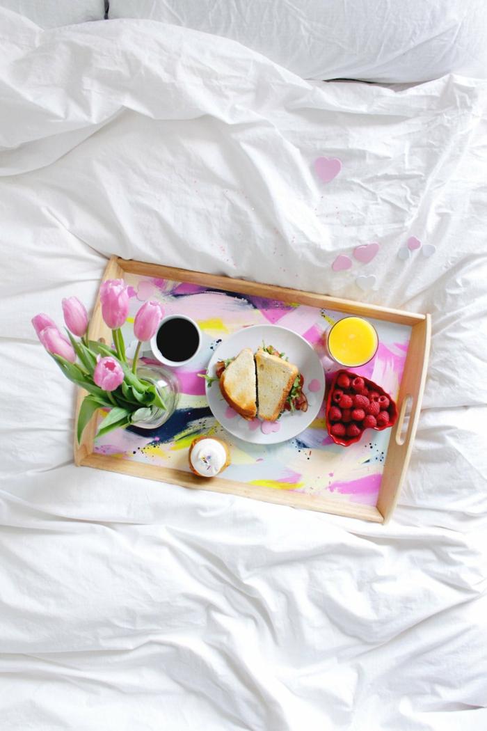 Frühstück im Bett zum Valentinstag, Toasts und Himbeeren, heißer Kaffee und Orangensaft, rosa Tulpen in Glasvase