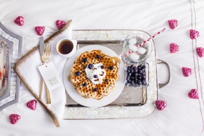 Frühstück im Bett zum Valentinstag, belgische Waffeln mit Sahne und Blaubeeren, heißer Kaffee und Wasser mit Eis