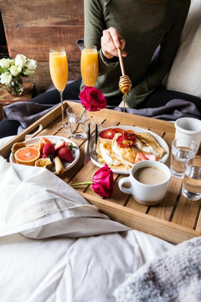 Frühstück im Bett zum Valentinstag, Pfannkuchen mit Honig und Früchten, Orangensaft und Cappuccino, rote Rosen