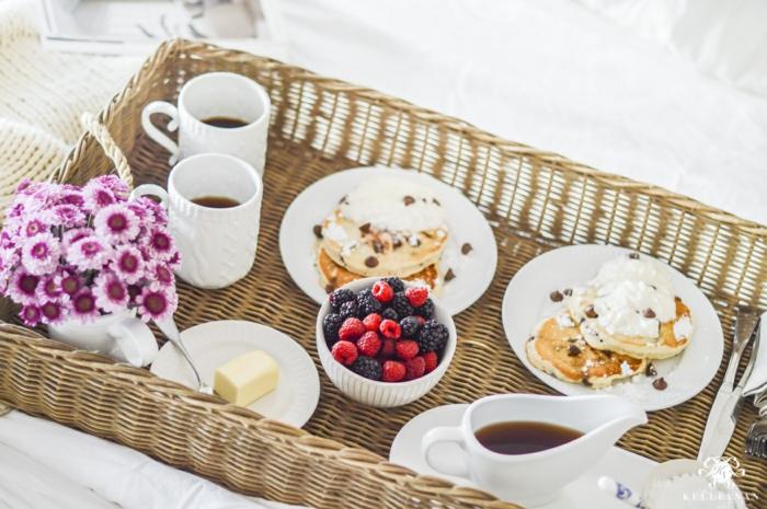 Frühstück im Bett zum Valentinstag, Pfannkuchen mit Eis und Beeren, heißer Kaffee und kleiner Blumenstrauß