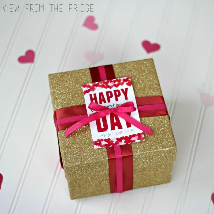 Geschenk zum Valentinstag schön verpackt, Schachtel mit goldenem Glitzer und roter Schleife, Anhänger mit Aufschrift