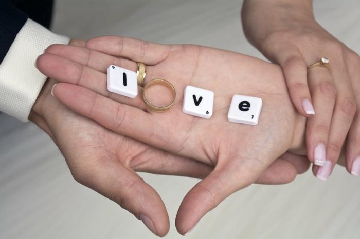 nach der Hichzeit hat das Paar das Wort Love mit O von Ehering geschrieben - Valentinstagsgrüße