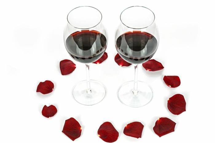 ein Bild mit schönen Valentinstagsgrüße - zwei Tasse roter Wein von Rosenblütten umgeben