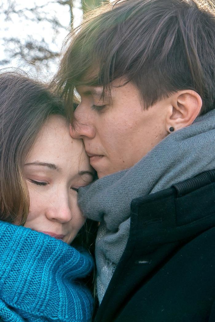 zwei Verliebte kuscheln, der Junge küsst sie sanft am Stirn - Verliebte Bilder
