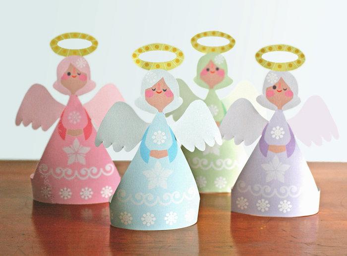 vier kleine engel aus papier - pinke, blaue, grüne und violette engel mit weißen flügeln und sternen - engel basteln mit kindern