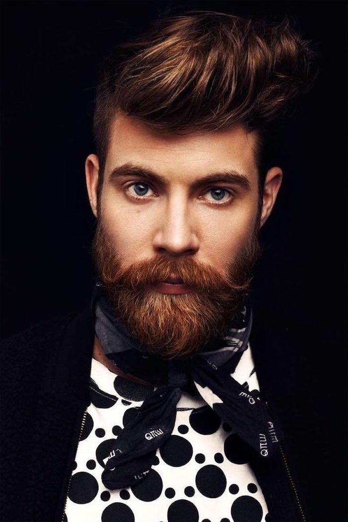 Kastanienbraune mittellange Haare und Vollbart, blaue Augen, weißes Shirt mit schwarzen Punkten, schwarzer Blazer