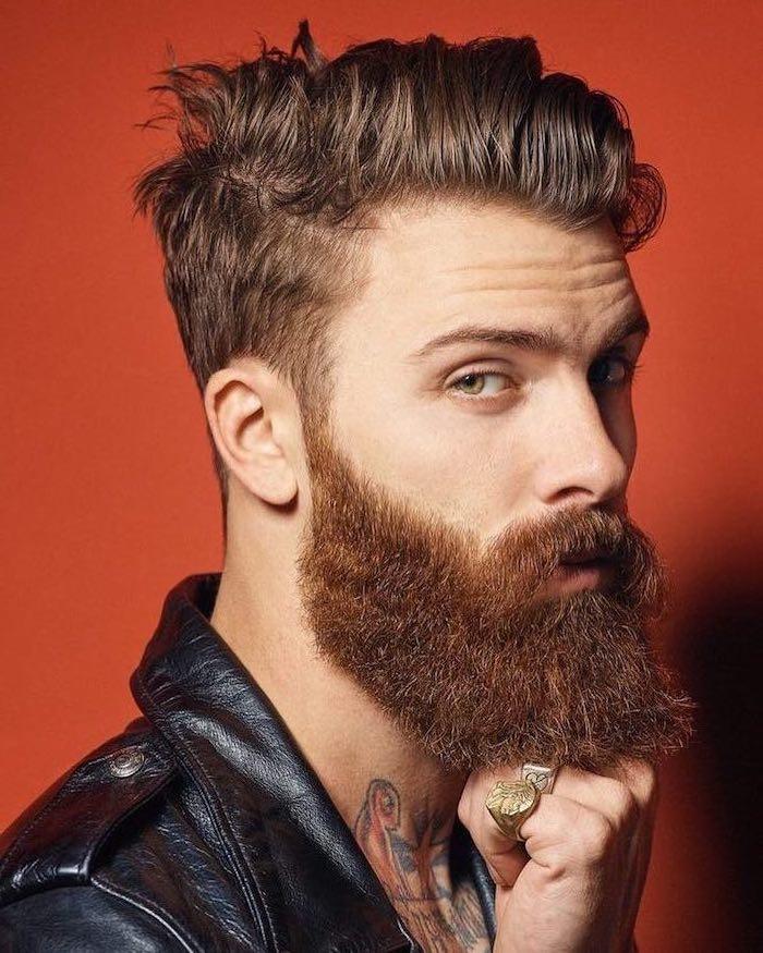 Mittellange kastanienbraune Haare und Hipster Bart, schwarze Lederjacke, Tattoos am Hals, massive goldene Ringe