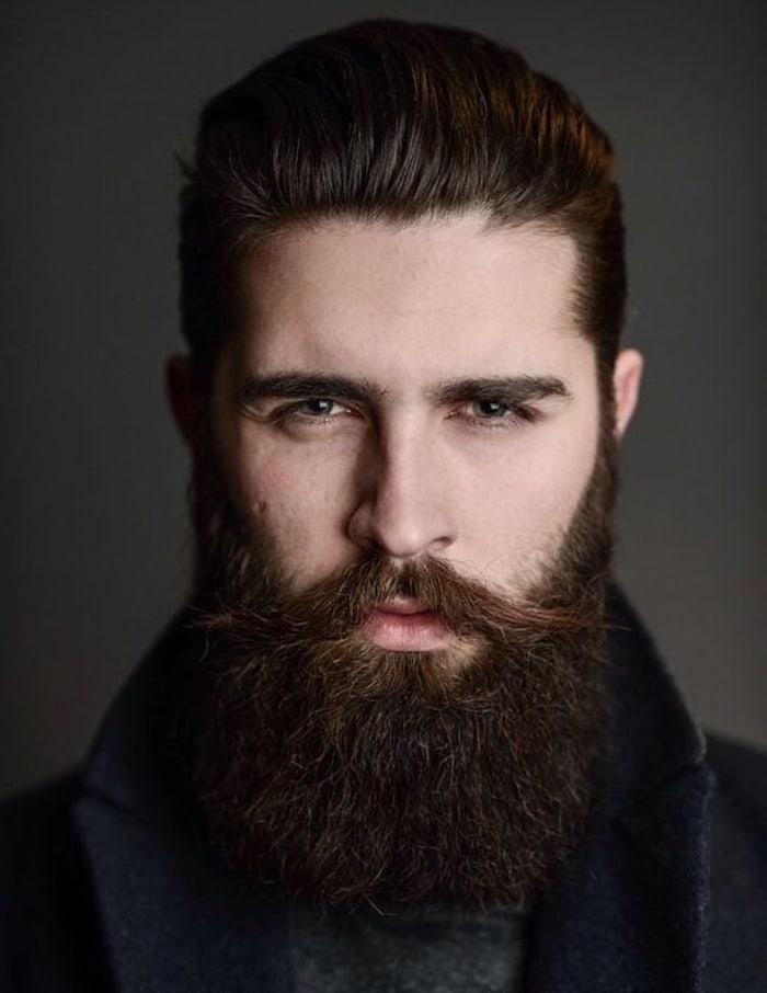 Dunkelbruane Haare und Vollbart, braune Augen und heller Hauttyp, schwarzer Mantel