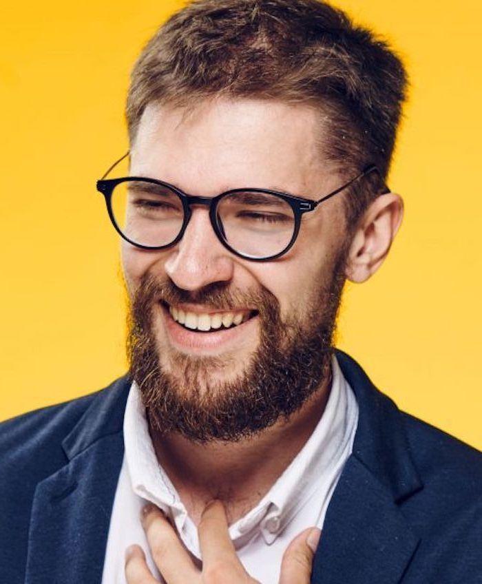 Kurzhaarfrisur und Vollbart, kastanienbraune Haare, Brille mit schwarzem Rahmen, weißes T-Shirt und dunkelblauer Blazer