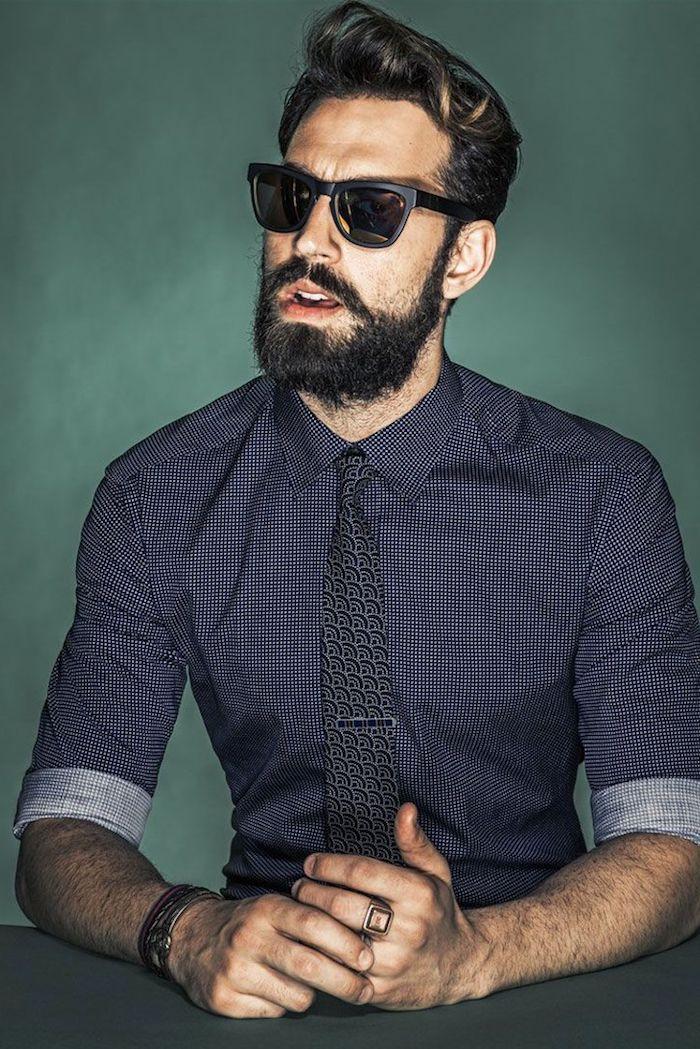 vollbart und coole frisur schwarz mit einer blonden strähne dunkelbraues hemd krawatte ring ray ban brille