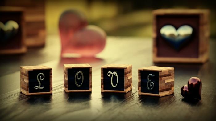 Auf Englisch das Wort Liebe auf vier kleine Würfel geschrieben - Valentinstagsgrüße
