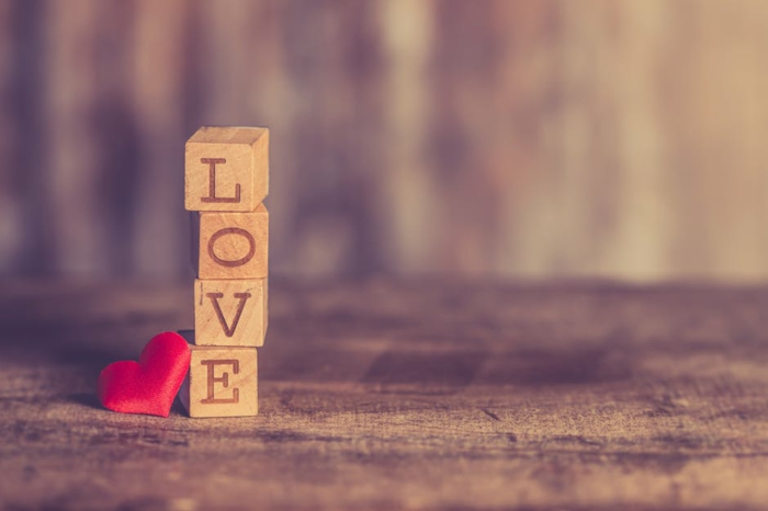 vier Würfel, die Love bilden und ein rotes Herz - Valentinstagsgrüße
