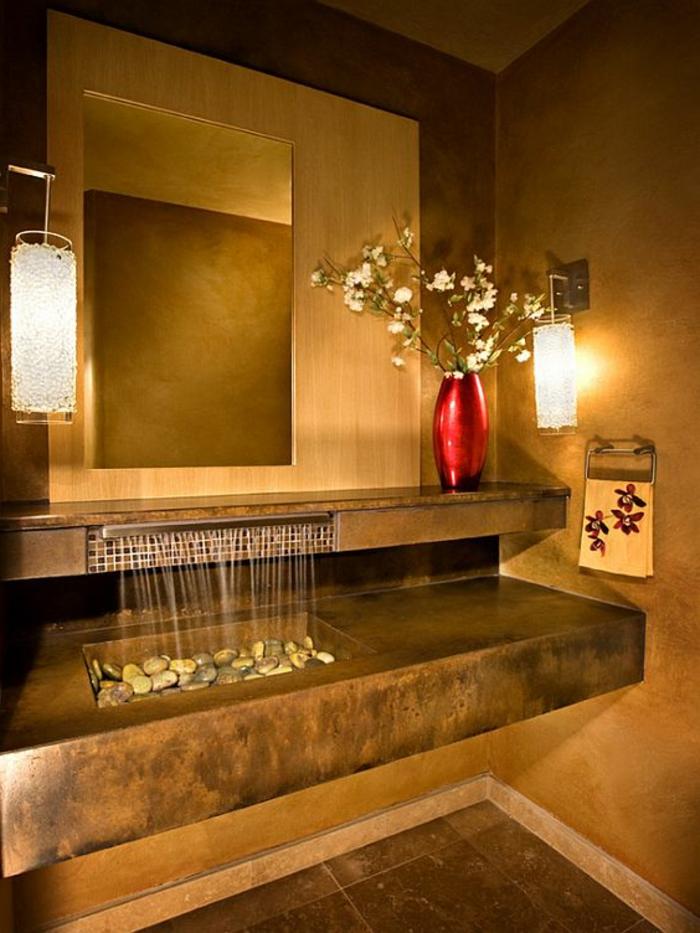 Badinterieur im japanischen Stil, Möbel mit simplen Formen, Möbel in Naturfarben, dekorative rote Vase mit einem Zweig mit weißen Blüten darin, Wand-Tuchständer mit einem Handtuch mit Blumenmotiv, Deko mit Flußsteinen, zwei Wandlampen auf den beden Seiten des Spiegels