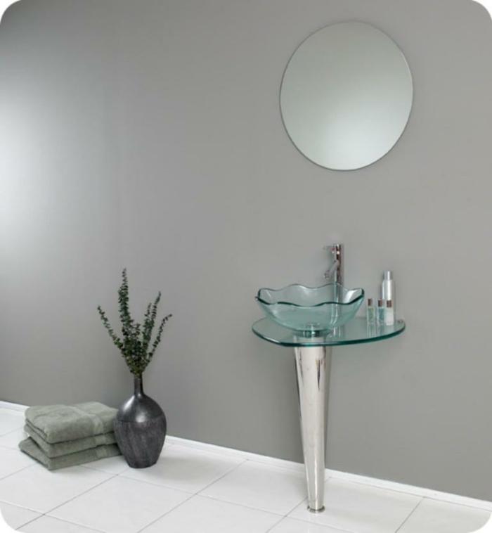 runder Wandspiegel über dem freistehenden Glasbecken, Bad mit grau gestrichener Wand und weißen Bodenfliesen, drei grüne Tücher neben einer grauen dekorativen Vase mit grünen Zweigen