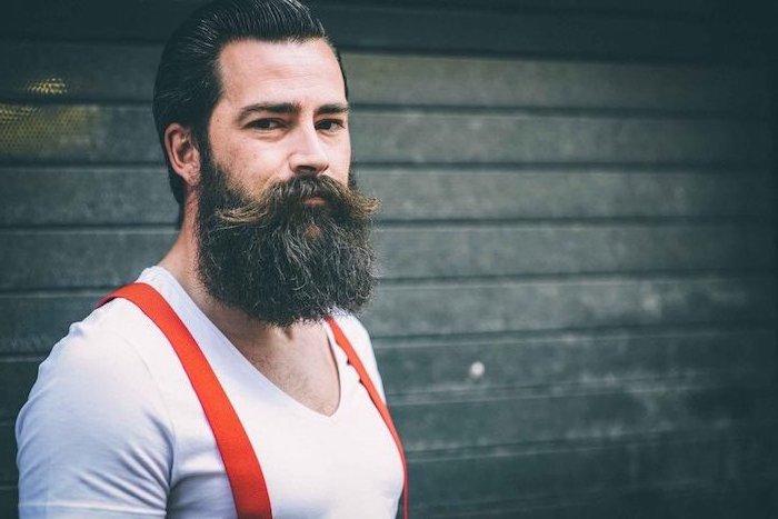 Mann mit Hipster Bart und glatten schwarzen Haaren, trägt weißes T-Shirt und rote Hosenträger