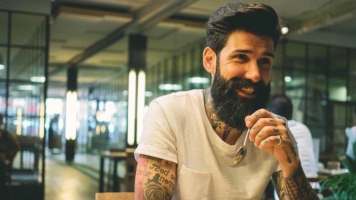Hipster Bart und glatte dicke Haare,weißes T-Shirt mit kurzen Ärmeln, viele Tattoos an den Armen und Fingern