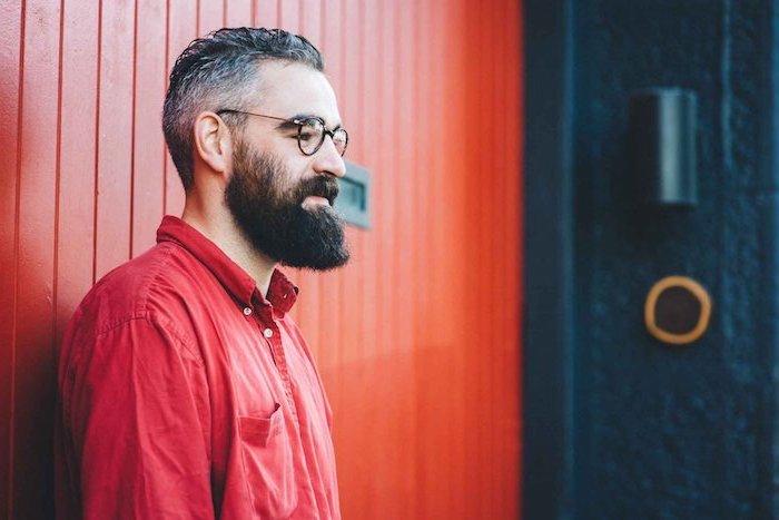 Herr mit Hipster Bart und Kurzhaarfrisur, trägt rotes Hemd, Brille mit schwarzem Rahmen