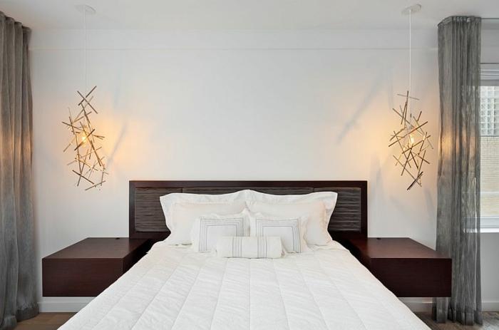 schneeweiße Bettwäsche, kleine Deko-Kissen mit Streifenprint, Designer-Kronleuchter aus Metall, bodenlange graue halbdurchsichtige Vorhänge