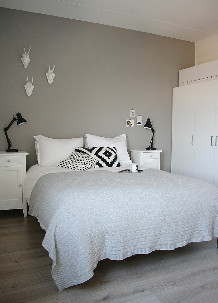 weiße Kissen mit schwarzem Print, graue Wand mit wei0er Wanddeko, schwarze Leselampe auf dem weißen Nachttisch