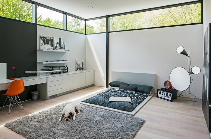 moderner Einrichtun in skandinavischem Stil - niedriges Bett mit grauer Bettwäsche, Stehlampe mit zwei Birnen und einem runden Spiegel, Fenster hoch an der Decke, Led-Beleuchtung, oranger Stuhl aus Plastik, ein Hund liegt auf dem Boden