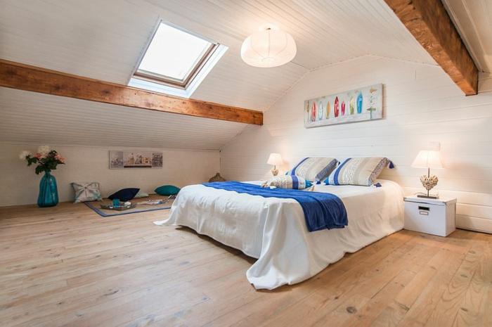 weiße Kiste mit Deckel dient als Nachttisch, zwei tragende Holzbretter, Zimmerdecke verkleidet mit Holz, blaue Kuscheldecke, drei Kissen mit Streifen, Relaxecke gestalten