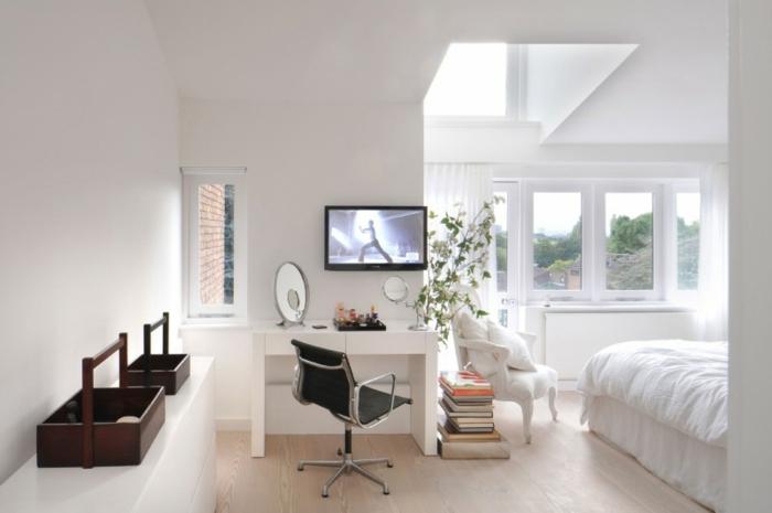 Armstuhl im vintagen Stil, weißer Schminktisch mit zwei Spiegeln - einem mit ovaler und einem mit runder Form, zwei Kisten aus dunklem Holz, kleines Fenster mit Waldaussicht, Fernseher montiert an der Wand