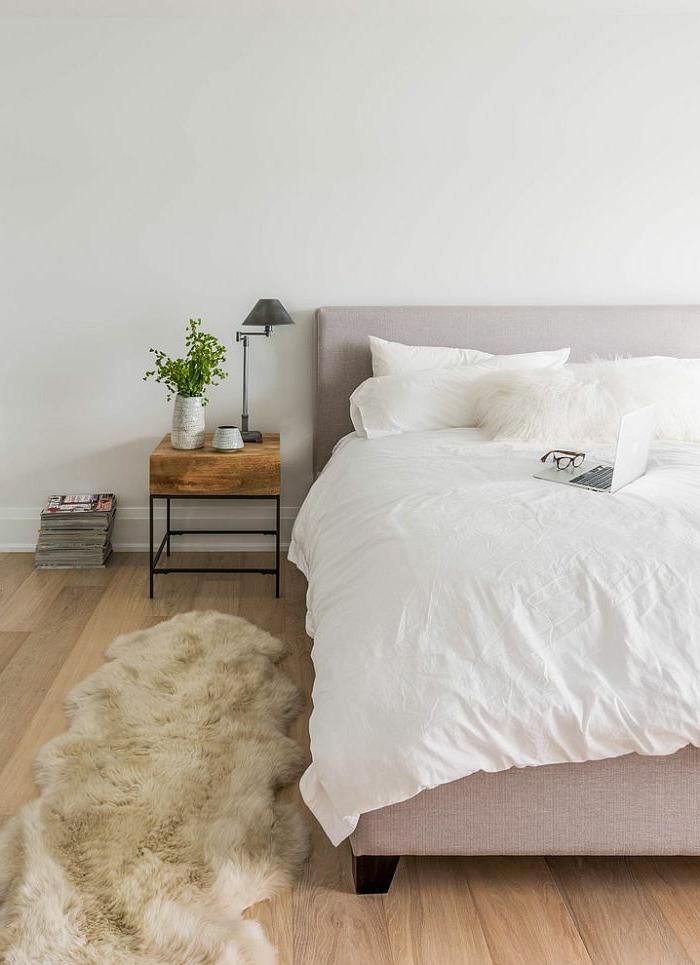 Bett mit Polsterkopfbrett, weißer Teppich aus Tierfell, ein Haufen Zeitungen, zwei dekorative Keramiktöpfe, Apple Laptop, schwarze Brille