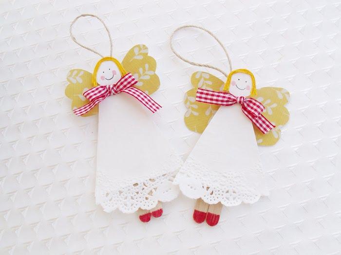 zwei kleine weiße engel mit gelben flügeln und weißen kleidern und mit roten schleifen und kleinen roten schuhen - engel aus eis-holzstäbchen