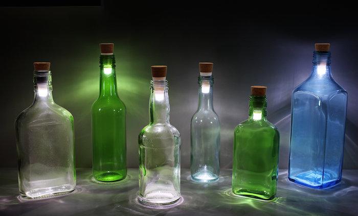 drei durchsichtige glasflaschen - flaschenlampen aus zwei grünen flaschen und einer großen blauen flasche - flaschenlampe selber bauen