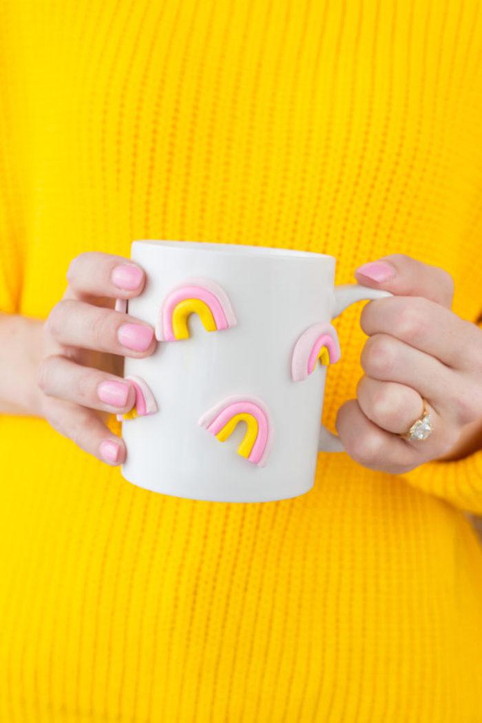 3D Tasse mit kleinen Regenbogen, gelber Pullover, goldener Ring mit Kristallstein, rosafarbener Nagellack