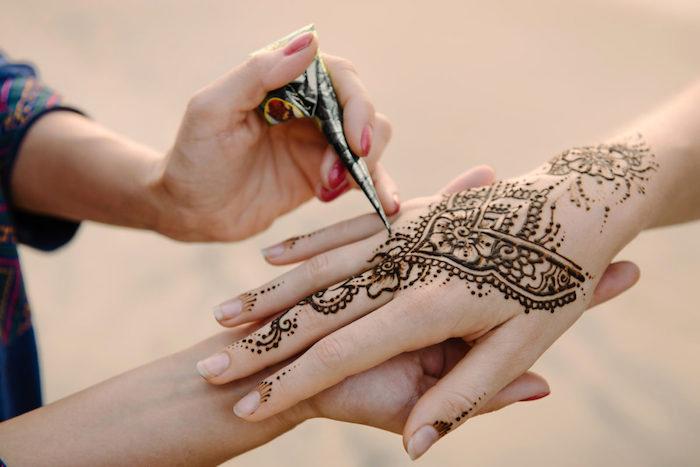 henna tattoo selber machen, temporäre tätowierung mit braunem henna am hand, hände verzieren