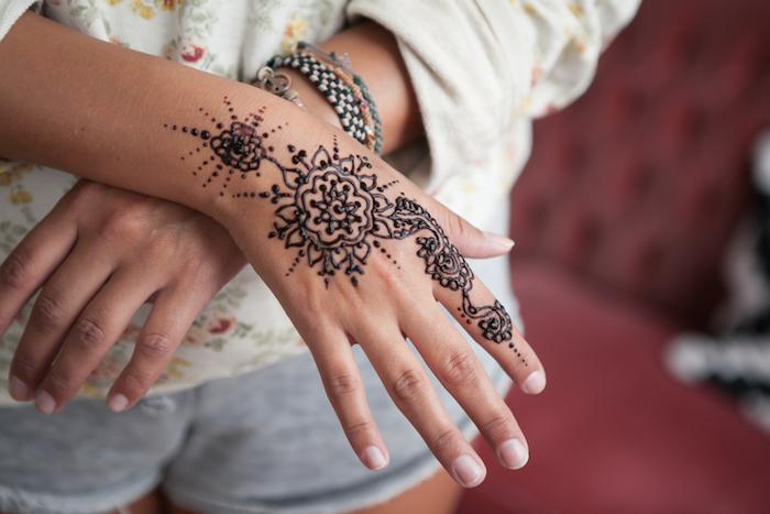 tattoo selber machen, frau mit temporärem tattoo an der hand, mehndi motive