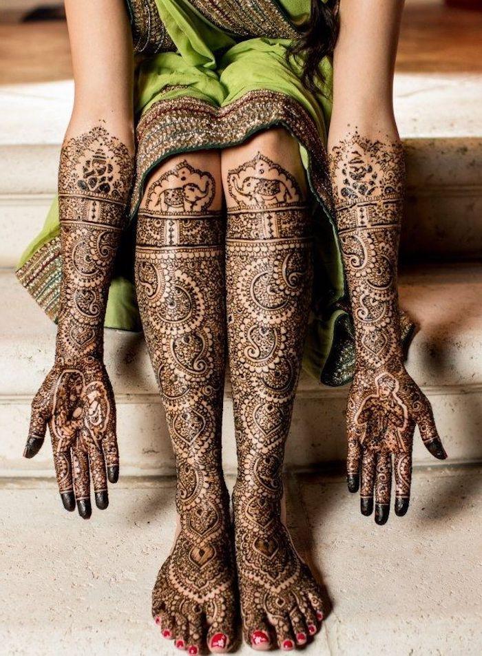 henna bilder, frau mit grünem sari und großen traditionellen temporären tätowierungen an den armen und an den füßen