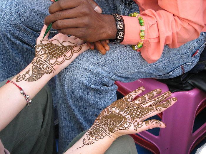 henna stift, hände mit braunem henna verzieren, henna muster, vogel
