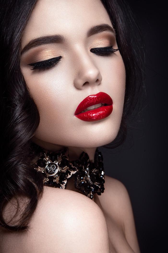 Knallroter Lippenstift, goldener Lidschatten und Lidstrich, schwarze Haare und Porzellanteint