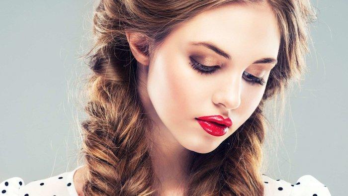 Goldener Lidschatten und schwarze Mascara, knallroter Lippenstift und Porzellanteint, kastanienbraune lange Haare, zwei Zöpfe