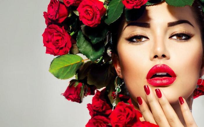 Schöne Frau mit braunen Augen, Lidstrich und schwarze Mascara, knallroter Lippenstift, roter Nagellack, Ohrringe mit kleinen Rosen und Rosenkranz