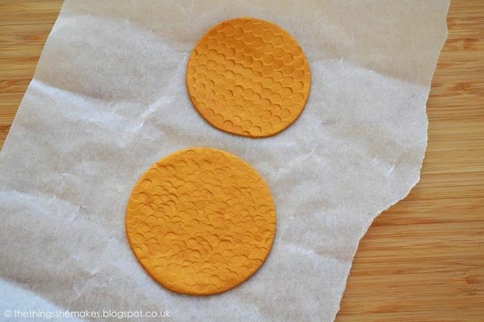 ein tisch aus holz und zwei figuren aus einer orangen fimo knete, fimo backen