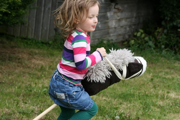ein garten und ein kleines mädchen, ein schwarzes steckenpferd mit einer weißen mähne, spielzeug für draußen, steckenpferd basteln kindergeburtstag