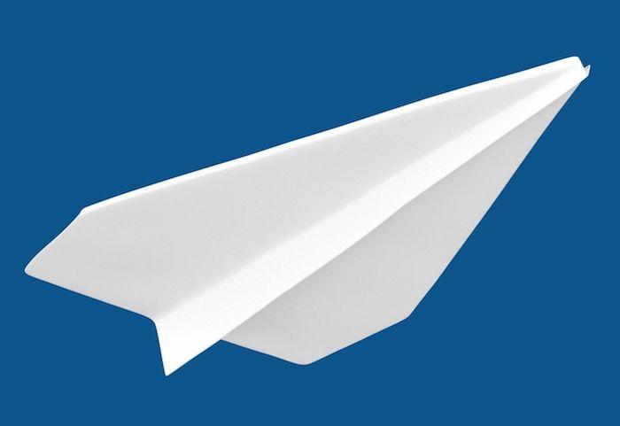ein großer weißer fleigender papierflieger und ein blauer himmel, papierflieger basteln, basteln mit papier