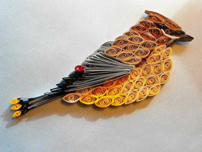 ein gelber quilling vogel mit grauen flügeln und mit schwarzen, gelben und grauen federn aus quillin papierstreifen, frühling basteln
